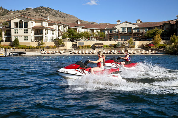 Two people riding jet skis on Osoyoos Lake in front of Walnut Beach Resort.