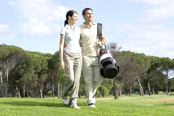 A couple walking together on a golf course with their clubs.