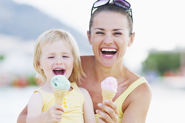 Mother and daughter smiling & eating ice cream cones on the private beach at Walnut Beach Resort.